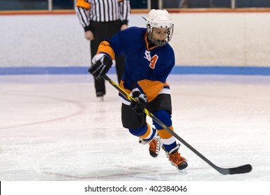 Young minor ice hockey player skating during a game in an arena