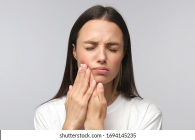 Young miserable woman experiencing severe toothache, pressing palm to cheek, closing eyes because of strong pain, isolated on gray background