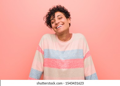 Young mixed african american teenager woman laughs and closes eyes, feels relaxed and happy.
