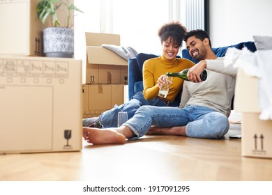 Young mixed ethnicity couple taking a break on moving day sitting on floor in lounge celebrating with champagne surrounded by removal boxes