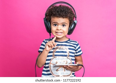 Young mixed race, african american, girl listening to music through big headphones, pink background