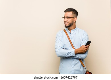 Young mixed race asian business man holding a phone smiling confident with crossed arms.