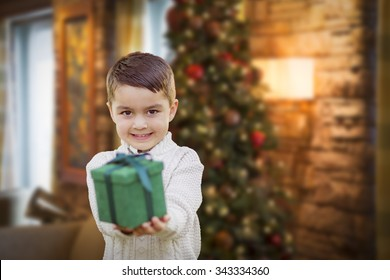 Young Mixed Race Boy Handing Gift Out Front with Christmas Tree Behind.