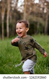 Young mixed race boy running excitedly through a green field, happy innocent childhood