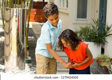Young mixed race brother and sister playing outside.