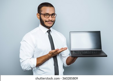 Young mixed race businessman with beard standing on grey background. Young man showing laptop