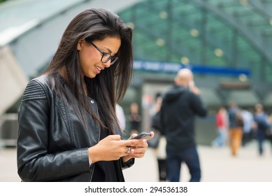 Young mixed race businesswoman portrait outdoors in Canary Wharf area in London with modern building as background while using smartphone.