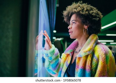 Young mixed race curly hair woman interacting with touchscreen terminal