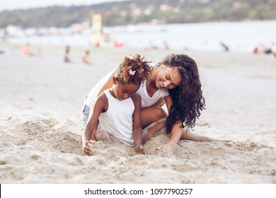 Young mixed race family sitting and relaxing at the beach on beautiful summer day.Mother playing with her daughter in the sand.