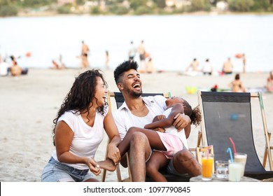 Young mixed race family sitting and relaxing at the beach on beautiful summer day.Parents making fun with they daughter.