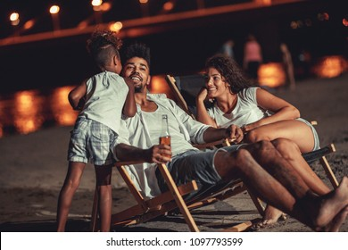 Young mixed race family sitting and relaxing at the beach on beautiful summer night.They sitting on sun beds and drink beer.