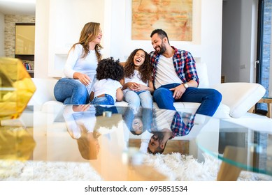 A young mixed race family sitting on the couch and having fun