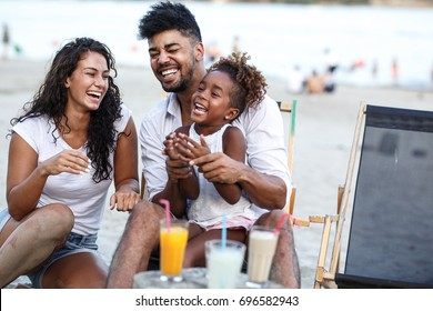 Young mixed race family sitting and relaxing  at the beach on beautiful summer day.Daughter lies in father lap and laughing.