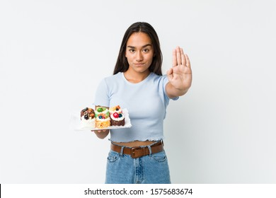 Young mixed race indian holding a sweet cakes standing with outstretched hand showing stop sign, preventing you.