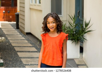 Young mixed race little girl standing outside.