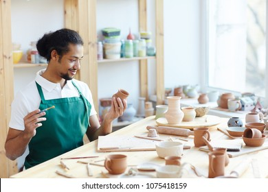 Young mixed race male potter sitting at workshop table, applying glaze on handmade clay pot with paintbrush and smiling