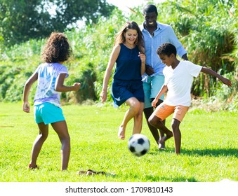Young mixed race parents with children having fun together outdoors, playing football on green grass