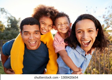 Young mixed race parents parents having fun piggybacking their children in the garden, looking to camera and laughing, close up