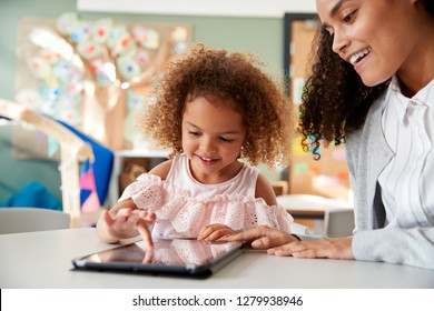 Young mixed race schoolgirl using a tablet computer with a female infant school teacher, working one on one together in a classroom, close up