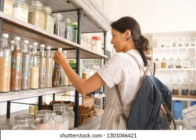 Young Mixed Race Woman Buying Superfoods in Zero Waste Shop. Lots of Healthy Food in Glass Bottles on Stand in Grocery Store. No plastic Conscious Minimalism Vegan Lifestyle Concept.