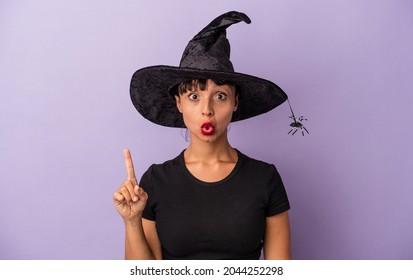 Junge gemischte Rasse Frau verkleidet als Hexe einzeln auf violettem Hintergrund mit einer großartigen Idee, Konzept der Kreativität.