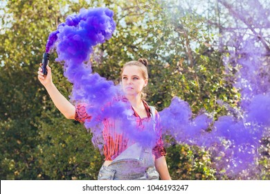 Young mixed race woman dressed in grungy hipster style outdoors poses with colored smoke bombs