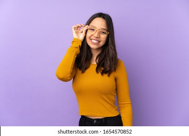 Young mixed race woman isolated on purple background with glasses and happy