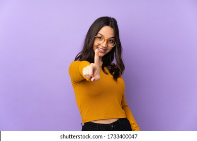 Young mixed race woman isolated on purple background showing and lifting a finger