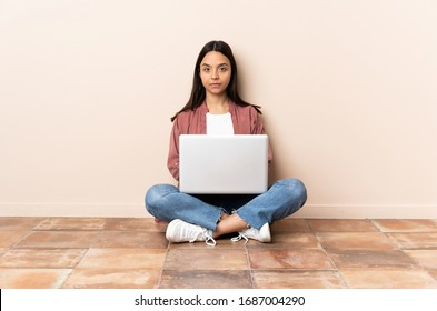 Young mixed race woman with a laptop sitting on the floor in back position