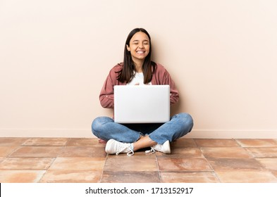 Young mixed race woman with a laptop sitting on the floor smiling a lot