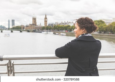 Young mixed race woman on a bridge in London. She is wearing a black coat and leaning on the railing while looking at Thames river and Big Ben on background. Tourism and lifestyle concepts.