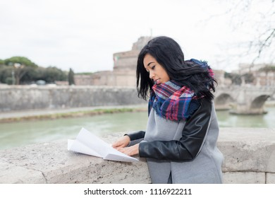 Young mixed race woman outside in the city, looking map.