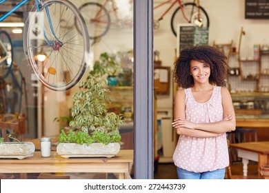 Young mixed race woman smiling while standing in the door of her cafe with her arms folded proud to be the owner of a small business