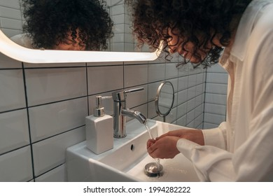 Young mixed race woman washing hands and face in a modern washroom. Curly hair female getting ready in the morning. Hygiene concept. At home concept.