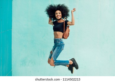 Young mixed woman with afro hair jumping outdoors. Female wearing casual clothes in urban background. Lifestyle concept