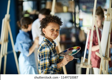 Young mixed-race boy with color palette standing by easel, looking at camera and painting at lesson