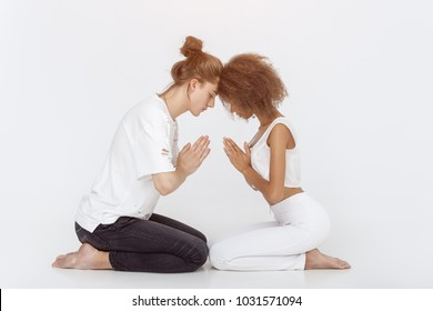 Young mixed-race couple practicing yoga indoors on white background. Young Afro-American woman and Caucasian man sitting in meditation lotus pose in tantra training school. Full length shot. Yoga