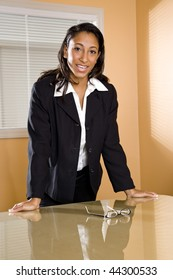 Young mixed-race Hispanic African-American female office worker standing in boardroom