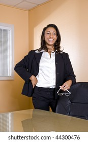 Young mixed-race Hispanic African-American woman laughing in office boardroom