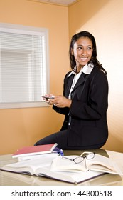 Young mixed-race Hispanic and African-American woman texting while studying