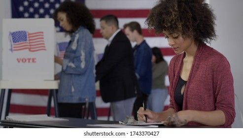 Young mixed-race woman staffing desk at polling station with various voters in background, US flag on wall behind them.