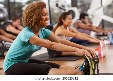 Young mixed-race woman stretching in a gym