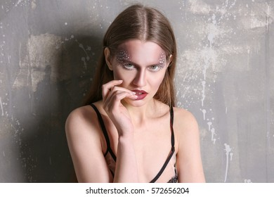 Young model with creative makeup near grunge wall