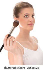 Young model doing make-up, focus on the brush