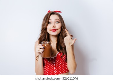 Young model eating chocolate cream from jar. looking at camera. isolated gray background