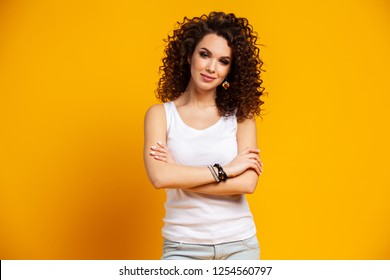 Young model expressing emotions while posing on indoor photoshoot. Stylish curly woman having fun in yellow studio.