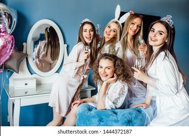Young, model friends ,celebrate hen party in luxury hotel apartament. Cheers with glasses of champagne.