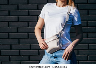 Young model girl in white t-shirt and glasses with waist bag against a black brick wall