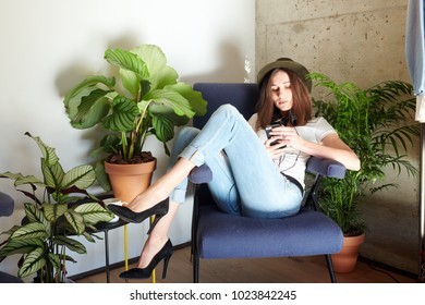 Young model in heels and denim lounging in armchair browsing smarpthone.