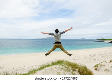 Young model jumping on a sand dune with open arms. White sandy beach and blue sky in the background. Scotland, UK.